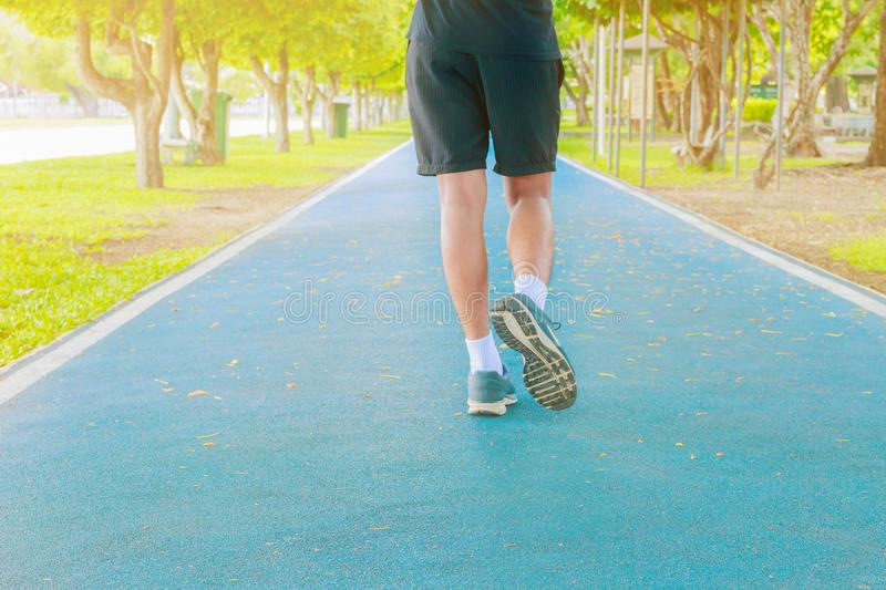 Running feet male in runner jogging exercise with old shoes for health lose weight concept on track rubber cover blue public park. Copy space add text stock photo