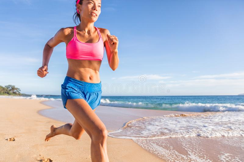 Running fitness runner woman training on beach. Asian girl working out cardio hiit workout. Weight loss active healthy lifestyle. In summer outdoors stock photo