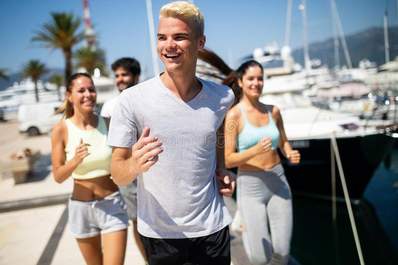 Running, friends, sport, exercising and healthy lifestyle concept. Happy people jogging outdoor. stock photos