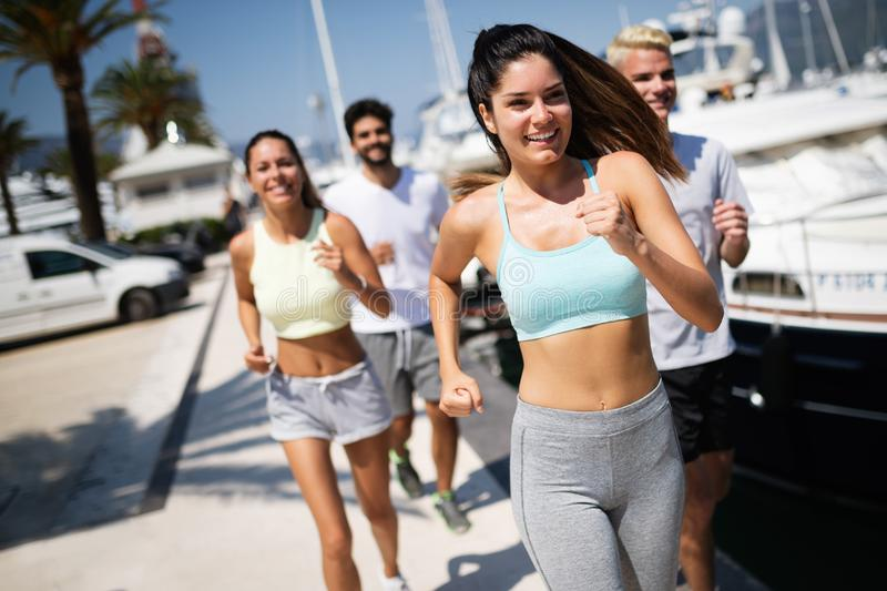 Running, friends, sport, exercising and healthy lifestyle concept. Happy people jogging outdoor. stock images