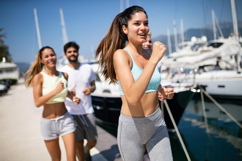Running, friends, sport, exercising and healthy lifestyle concept. Happy people jogging outdoor. royalty free stock photo