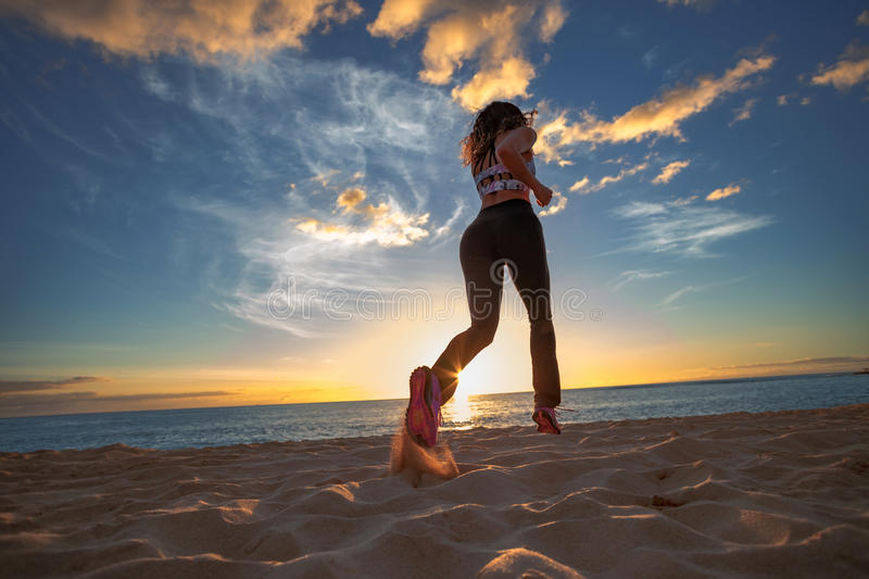 Fit girl jogging on a beach against sunset sky on sea background royalty free stock image