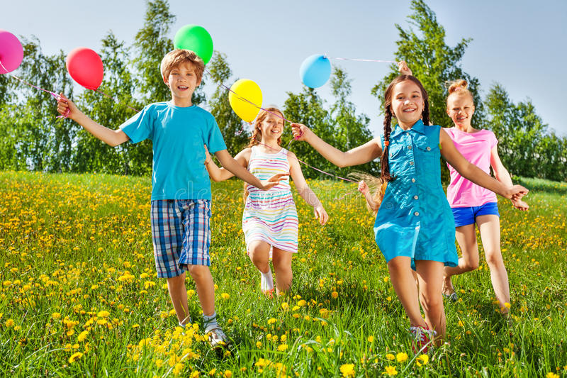 Running happy kids with balloons in green field royalty free stock images