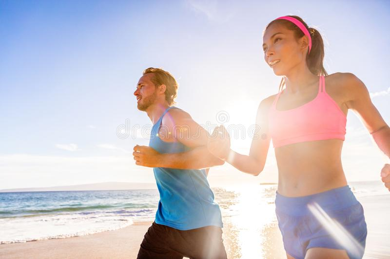Running healthy people training together. Health, exercise, weight loss concept. Couple living an active lifestyle doing morning. Beach jog stock photos