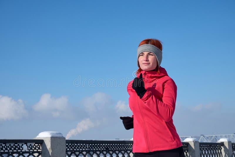 Running idrottsman nenkvinna som sprintar under vinterutbildning utanför i kallt snowväder Stäng sig upp uppvisning av hastighet  royaltyfria bilder