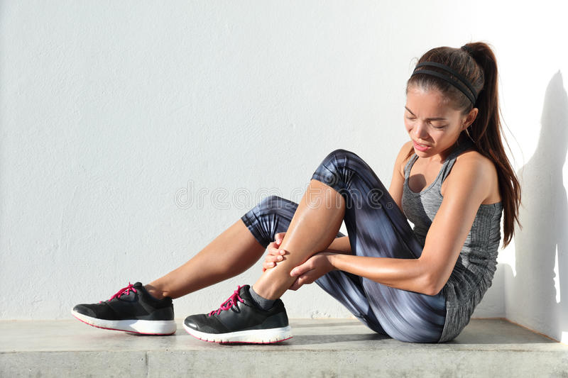 Running injury leg pain - sport woman runner holding painful sprained ankle. Running injury leg accident- sport woman runner hurting holding painful sprained royalty free stock images