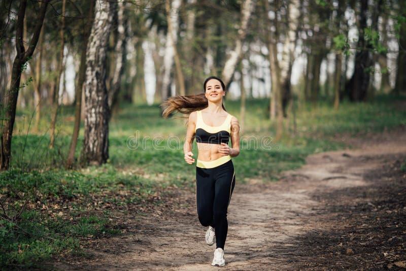 running kvinna Kvinnlig löpare som joggar under utomhus- genomkörare i en parkera royaltyfri foto