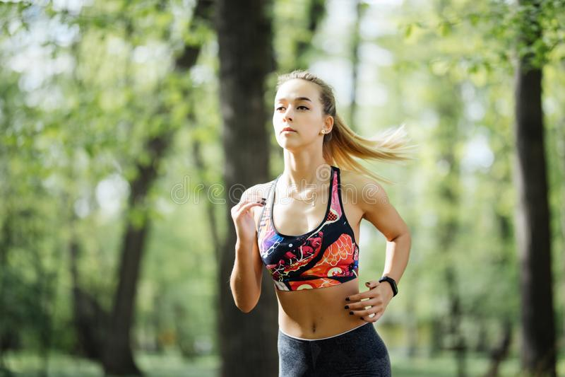 running kvinna Kvinnlig löpare som joggar under utomhus- genomkörare i en parkera Härlig passformflicka model kondition utomhus i royaltyfria foton