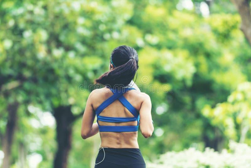 running kvinna Sportkvinnor som joggar under utomhus- genomkörare i, parkerar arkivbild