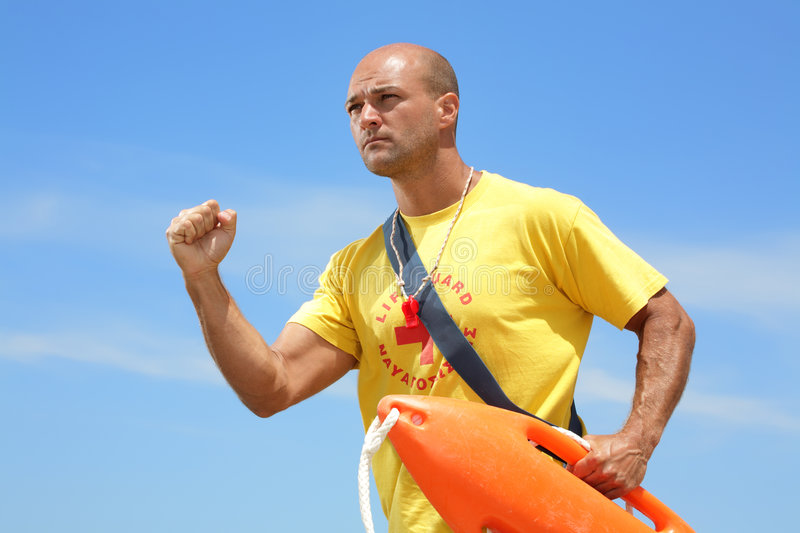 Running lifeguard. A male lifeguard running to help, holding a float (lifeguard rescue can royalty free stock images