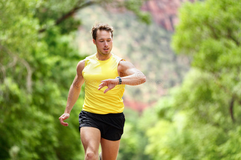 Running man looking heart rate monitor smartwatch. Running looking at heart rate monitor smartwatch while running. Male runner jogging outside looking at sports stock photos