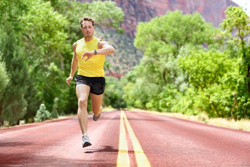 Running man looking heart rate monitor smartwatch. Running man sprinting looking at heart rate monitor smartwatch on run. Man jogging outside looking at his stock photos