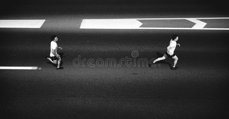Running man - male runner jogging outdoors on-road training for marathon run as part of healthy lifestyle. stock photo