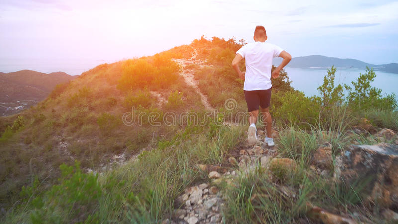 Running man on mountain road. Sport fitness boy exercising outside in mountains. Living healthy lifestyle enjoying royalty free stock image