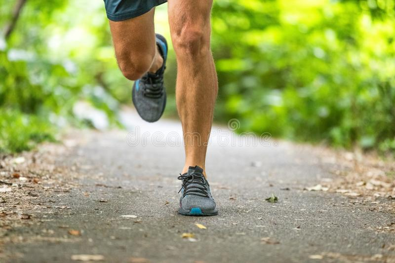 Running man runner athlete workout jogging outdoors on city park path with running shoes closeup of feet. And legs royalty free stock photo