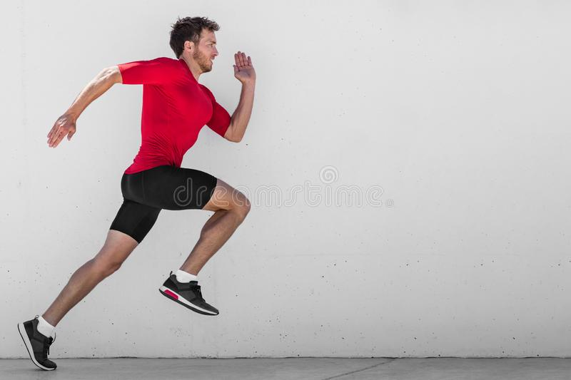 Running man runner training doing outdoor city run sprinting along wall background. Urban healthy active lifestyle. Male athlete. Doing sprint hiit high stock images