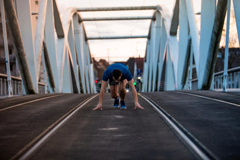 Male athlete running. Running man runner training doing outdoor city run sprinting over a bridge. Urban healthy active lifestyle. Male athlete running over royalty free stock photography