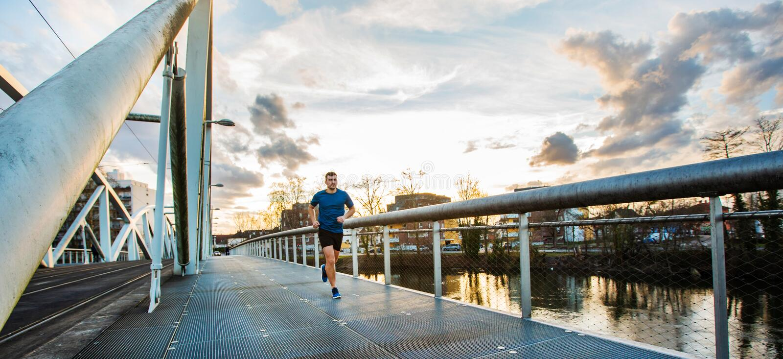 Running man runner training doing outdoor. City run sprinting over a bridge. Urban healthy active lifestyle. Male athlete running over sunset background royalty free stock photos