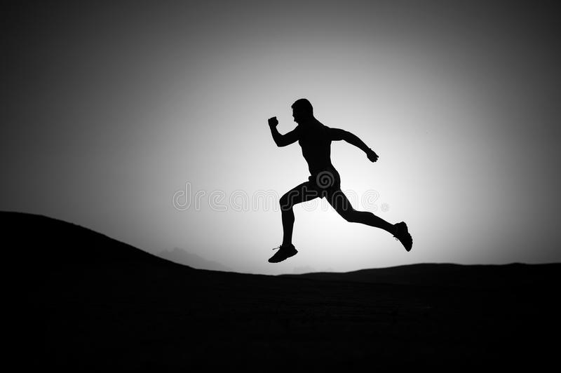 Running man silhouette at sunset sky royalty free stock images