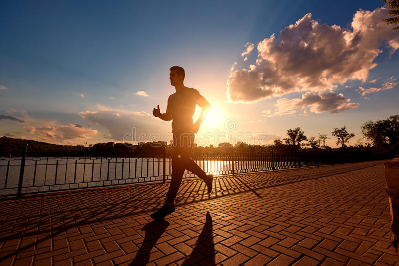 Running man silhouette in sunset time. royalty free stock photography
