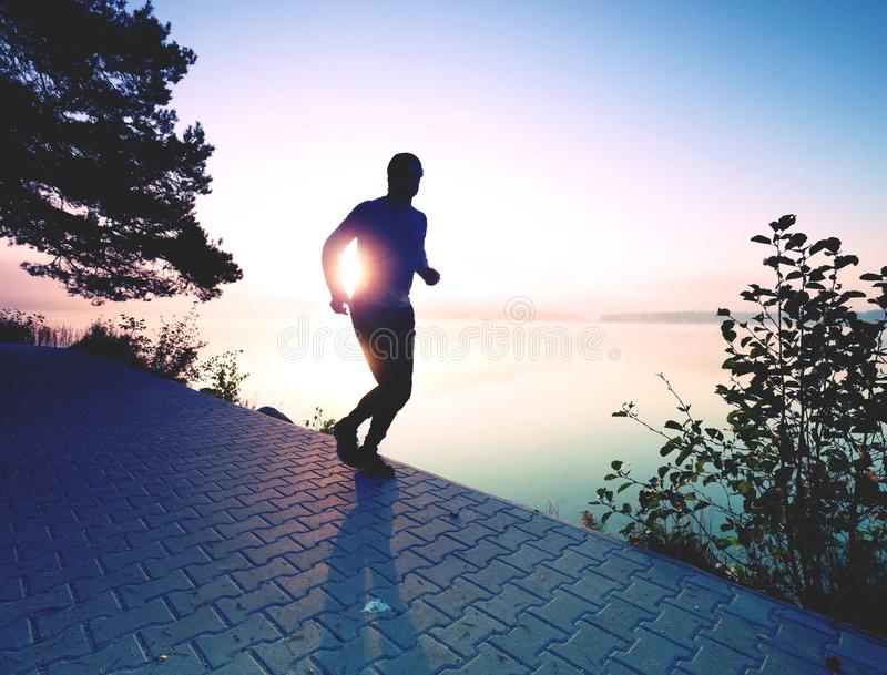 Running man wear dark running shoes and trendy sports clothes. Sportsman exercising at lake shore or river bank stock photo