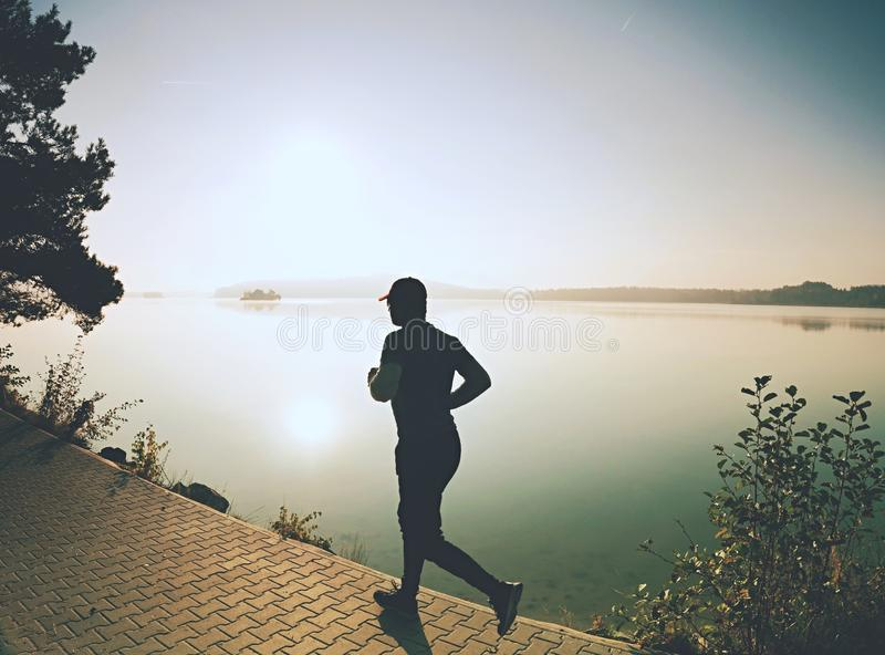 Running man wear dark running shoes and trendy  sports clothes. Sportsman exercising at lake shore or river bank young workout training track strong sprinting royalty free stock images