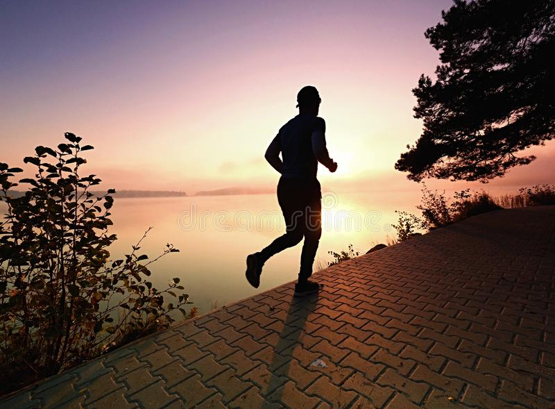 Running man wear dark running shoes and trendy sports clothes. Sportsman exercising at lake shore or river bank royalty free stock images