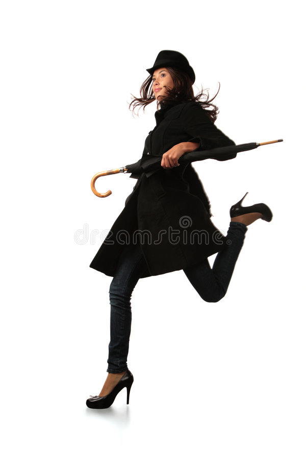 Running model. Fashion model in black with umbrella running over white background royalty free stock photo