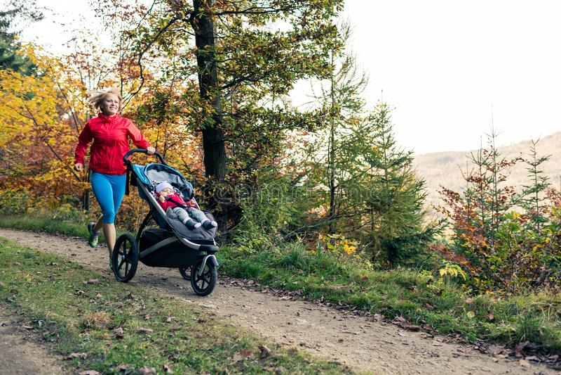 Running mother with stroller enjoying motherhood at autumn sunset stock photography