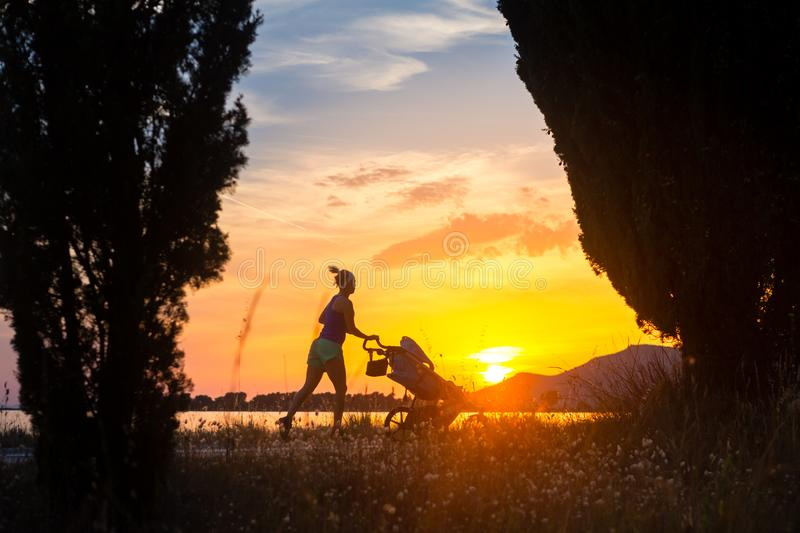 Running mother with stroller enjoying motherhood at sunset lands royalty free stock photography