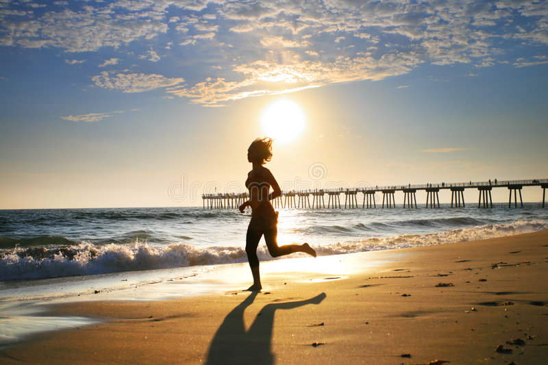 Running by the ocean. Woman at the beach running by the ocean at sunset stock image
