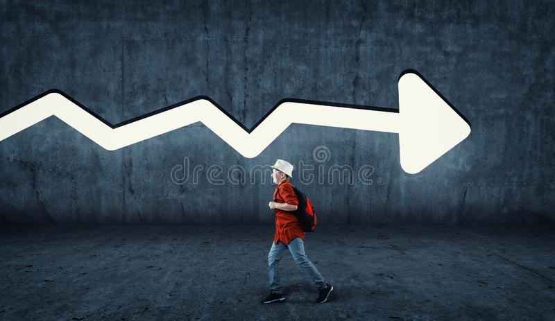 Running opposite direction. Young man running in the opposite direction . Running angaist the wall painted with an arrow in opposite direction stock photography