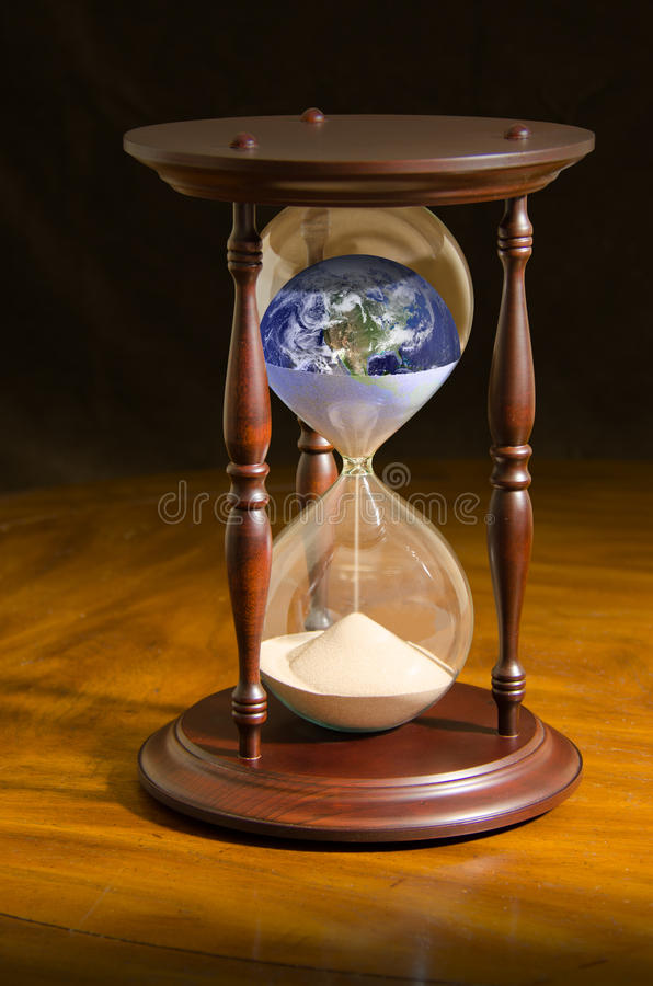 Running out time climate change eco apocalypse. A very dramatically lit photo of a large hour glass with the Earth inside of it with the Earth slipping away stock photos