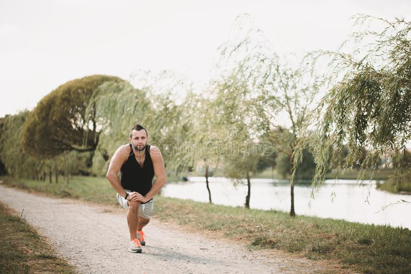 Running in the park. Active sport concept. Healthy sportsman does exercises on the street. Tired athlete in sportswear. Get a pause stock images