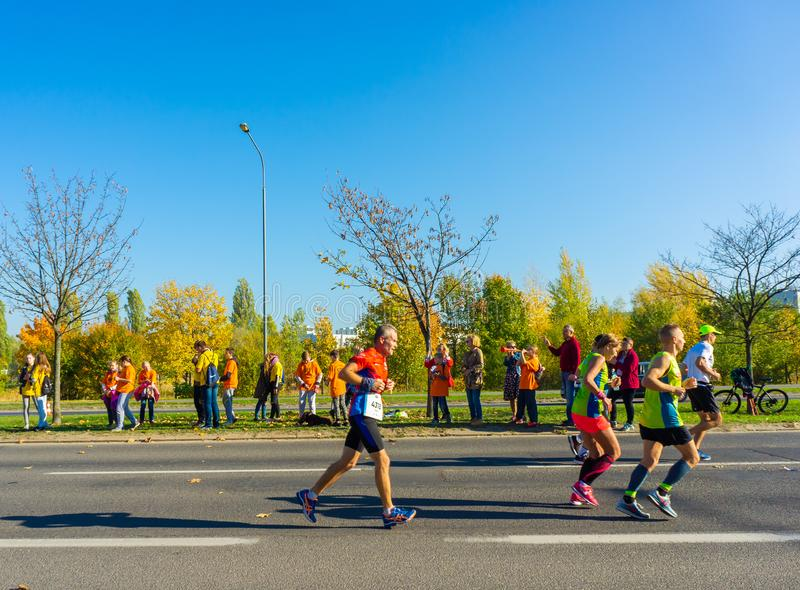 Running people. Poznan, Poland - October 14, 2018: Many people running on a street during the PKO Poznan Marathon on a sunny day in the autumn season. The event stock photos