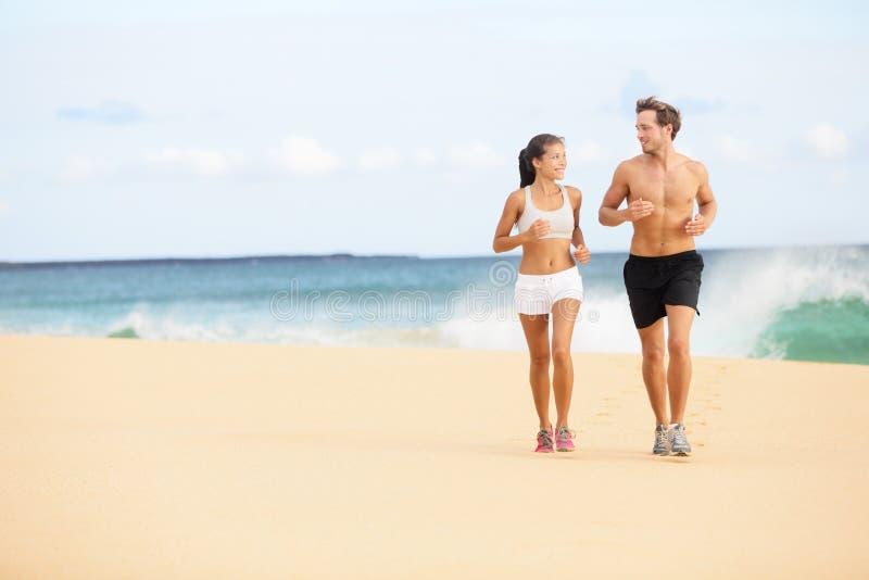 Running people - runners couple on beach run stock image
