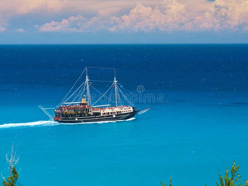 Running pirate corsair style boat ship in amazing Greece island bay with swimming people, beach in Ionian Sea blue water, Famous G. Reece islands holidays royalty free stock image