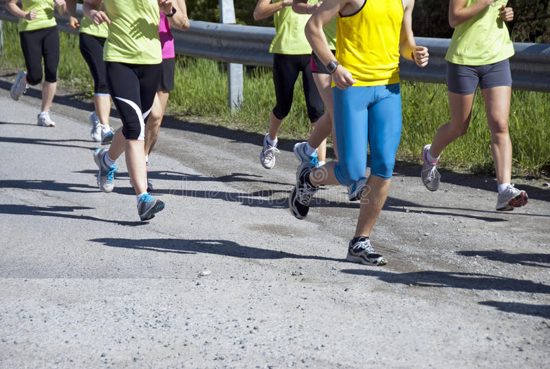 Running racers. Group of marathon racers - legs detail royalty free stock images