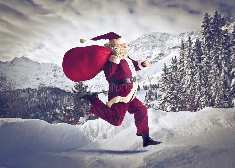 Running Santa Claus. Santa Claus running on a white mountain royalty free stock photos