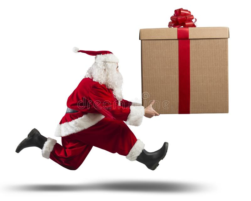 Running Santa Claus with big gift royalty free stock images