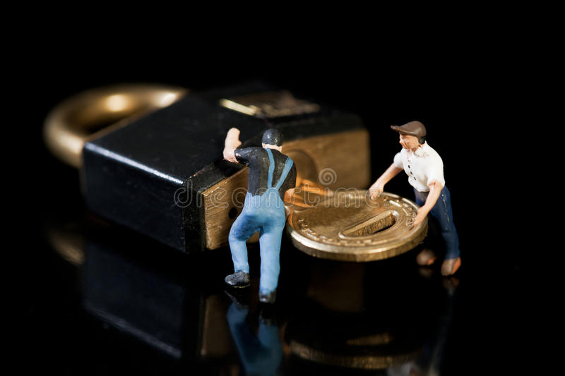 Running A Security Check. Two miniature figures of workmen turning a key in a padlock to check up on security on a dark background stock photos