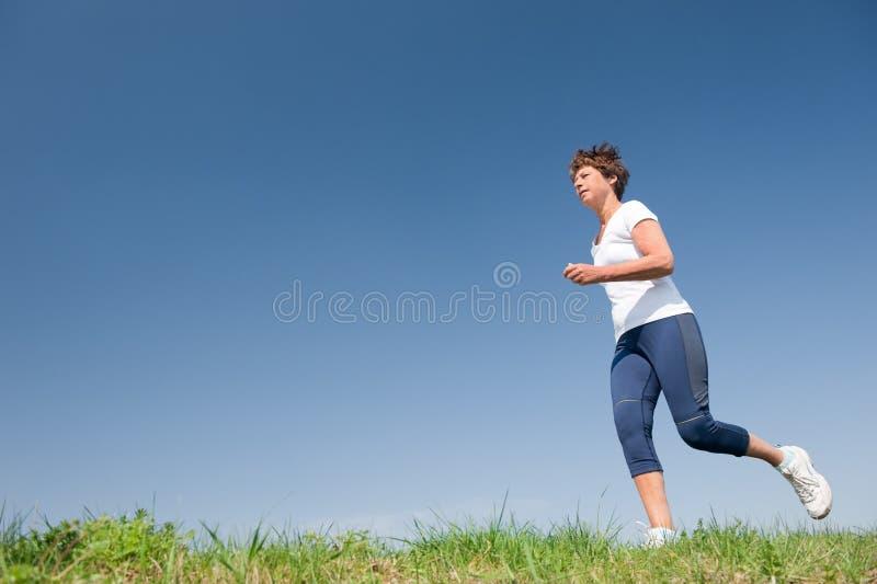 Running senior woman stock photography