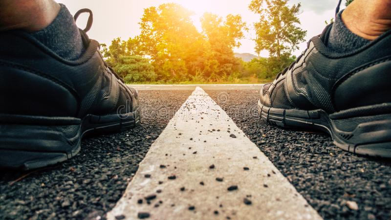 Running shoes, athlete running sport feet on asphalt road with straight white line and sunset background royalty free stock photos