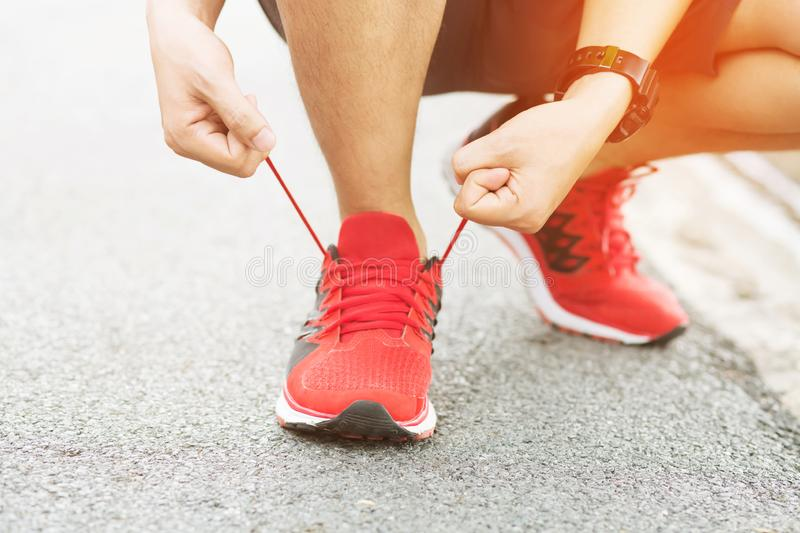 Running shoes. Barefoot running shoes closeup. male athlete tying laces for jogging on road. stock images