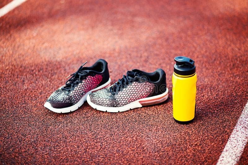 Running shoes and bottle of water on racetrack stock photo