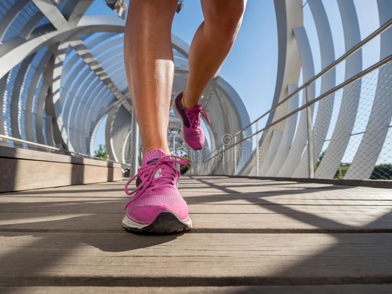 Running shoes closeup of a female runner on a modern bridge. stock photography