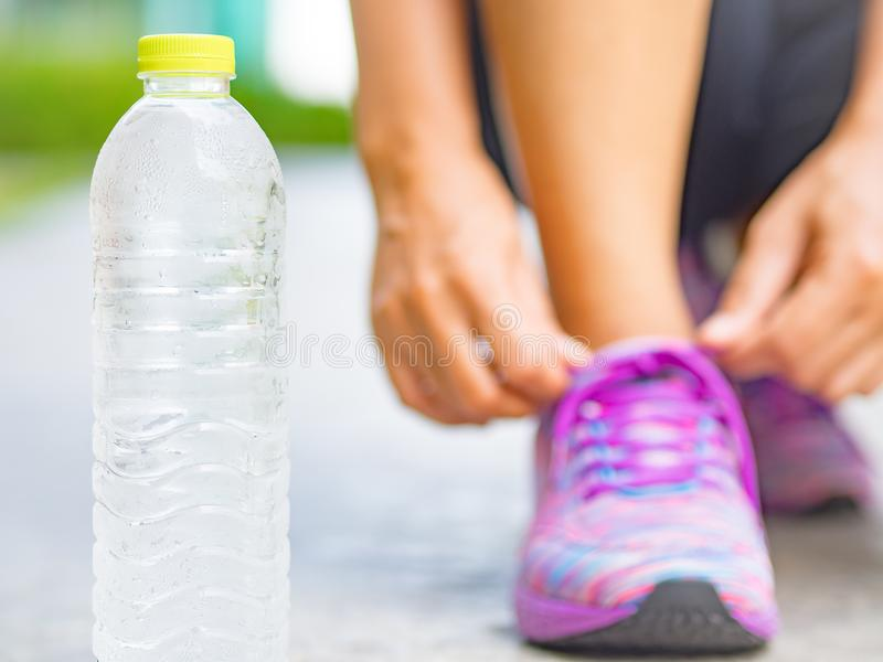 Running shoes - closeup of water bottle and woman tying shoe laces. Female sport fitness runner getting ready for jogging in garden background royalty free stock photography