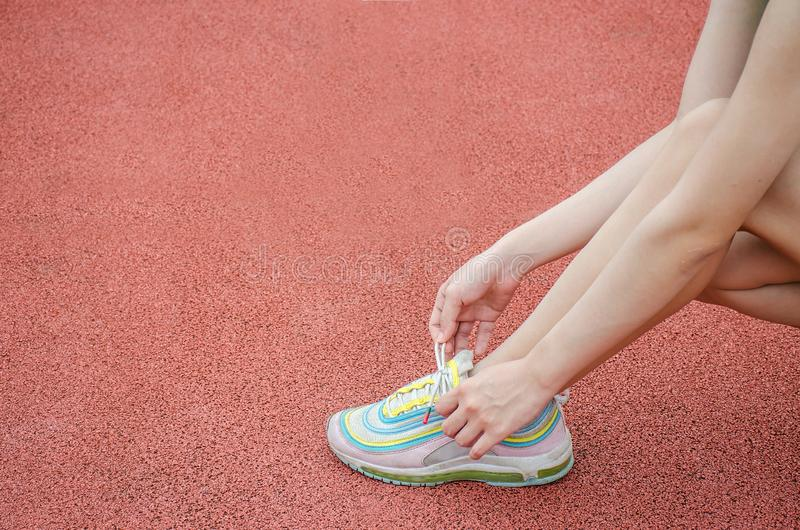 Running shoes - closeup of woman tying shoe laces. Female sport fitness runner getting ready for jogging outdoors on the lanes of stock image