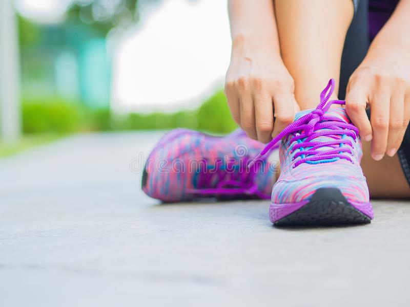 Running shoes - closeup of woman tying shoe laces. Female sport fitness runner getting ready for jogging stock photos