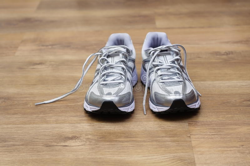 Running shoes on a gym floor after workout. Womans new running shoes on a gym floor just after workout royalty free stock photography